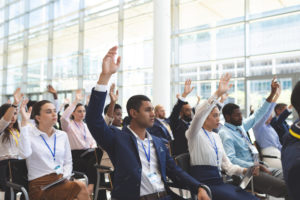 Front view of diverse business people raising hands in business seminar in office building